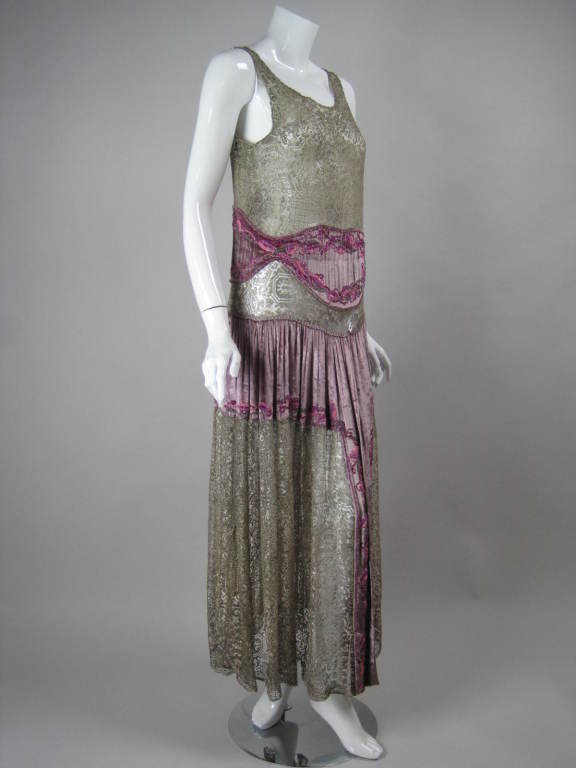 Stunning 1920's Art Deco metallic lace dress has lilac silk velvet inserts with hand-beaded adornment.  Sleeveless.  Scoop neck.  Center front slit. Bodice is lined; skirt is not.  No closures.