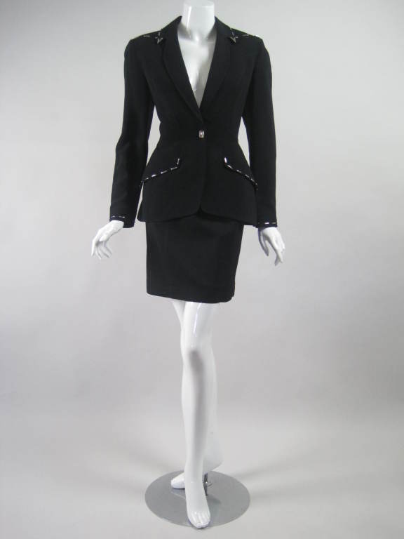 Skirt suit from Thierry Mugler is made out of black viscose with silver-toned rectangular metal studded accents.  Single-breasted blazer has single snap closure, notch lapel, and flap pockets.  Straight skirt has waistband and zipper closure. Both