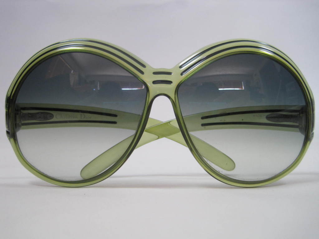 Oversized Christian Dior sunglasses are made of transparent green plastic with a darker green double line that outlines part of the frame. Gradient light gray lenses. CD logo at temples.