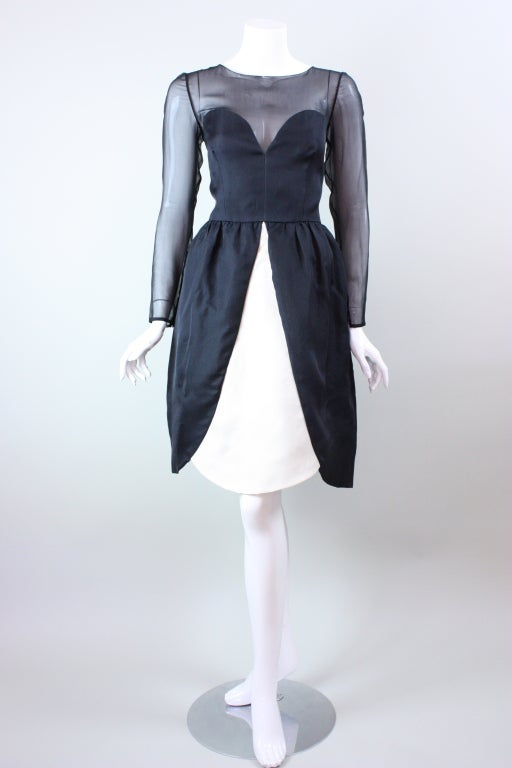 Bill Blass cocktail dress circa 1980's is made out of black silk organza with black silk chiffon that covers the chest and arms.  Fitted bodice has a round neckline and long tapered sleeves with three covered button closures.  Full skirt is pleated