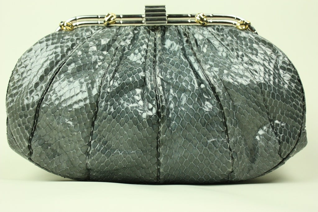 Fun handbag from Judith Leiber is made out of gray snakeskin and features gold-toned frog hardware.  Bag is oval-shaped with gathering at frame that releases into soft pleats.  Interior is lined with light gray faille and has side pocket.
