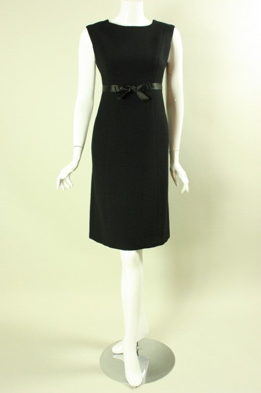 Lovely 1960's shift dress from Gustave Tassell is made of black wool crepe.  It features a round neckline, princess seams, an a-line skirt, and satin waistband that ties into a bow at the center front.  Fully lined.