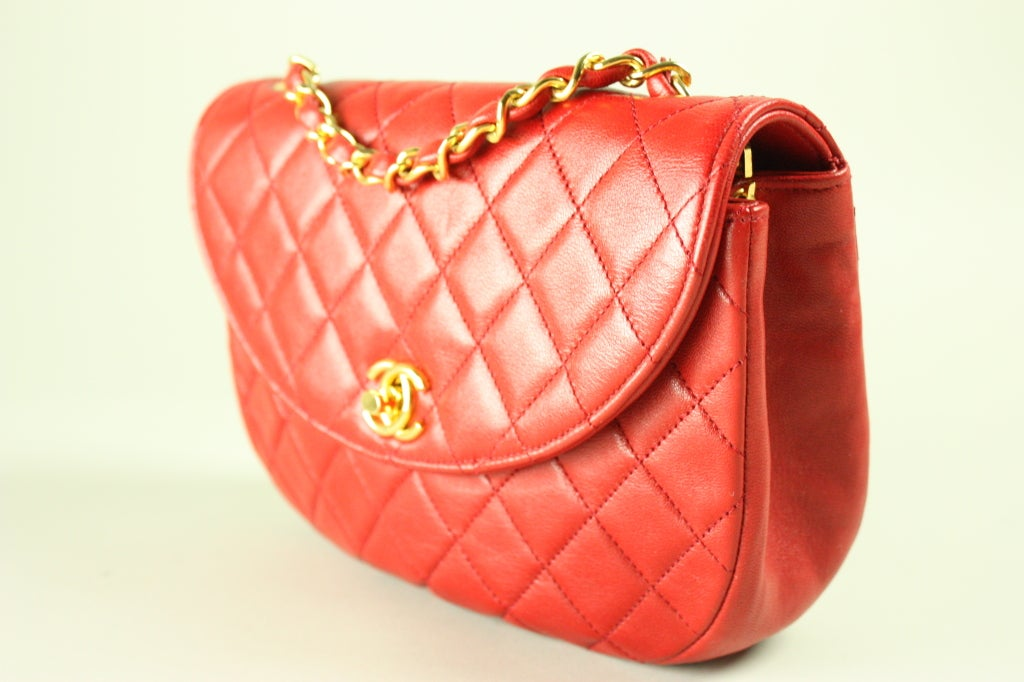 Mini handbag from Chanel is made out of quilted buttery red leather.  Gold-toned hardware.  Chain strap.  Comes with authenticity card, which matches the serial number on the bag's hologram.  Original dust bag included.