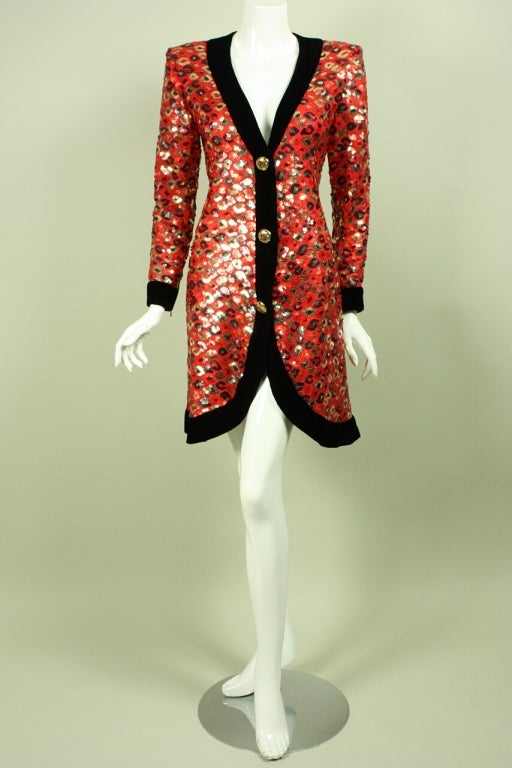 1980's party dress from Givenchy is made of red silk chiffon with a leopard-like pattern in black and gold sequins.  Deep v-neck.  Long tapered sleeves have zipped cuffs.  Black velvet trim along neckline, cuffs, and hem.  Center front decorative