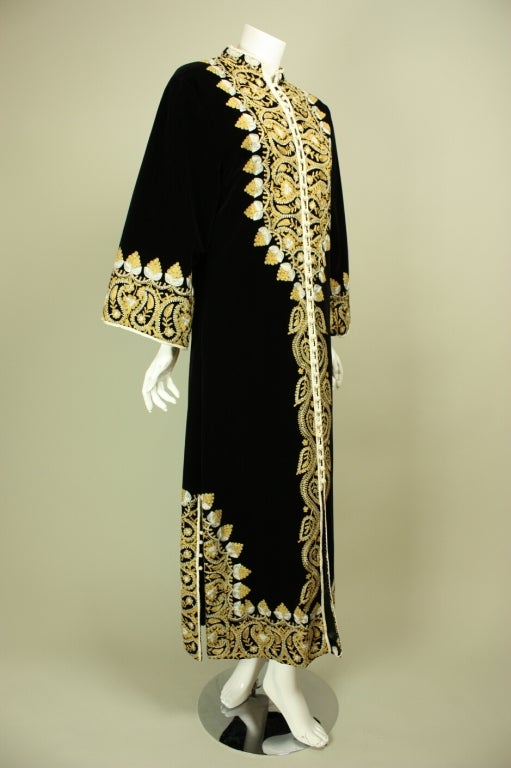 Heavily,embroidered caftan originated in Morocco and dates to the 1960's.  It is made of jet black velvet with yellow and white machine-embroidery down the center front, cuffs, hem, and at center back.  Mandarin collar.  Center front looped closures