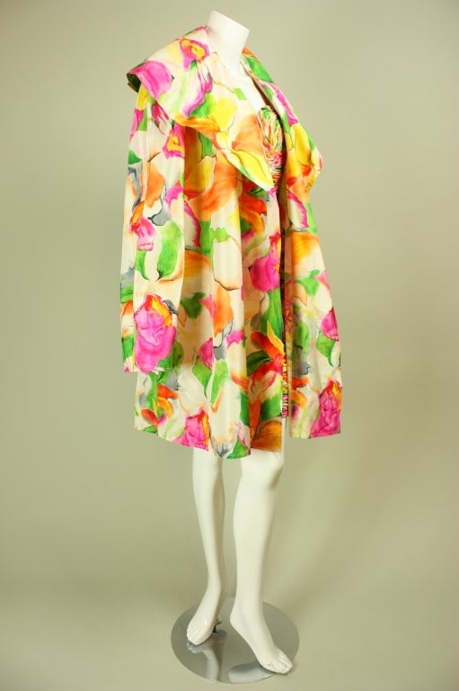 Two-piece ensemble from Vicky Tiel Couture dates to the 1980's through early 1990's.  Multicolored floral print in shades of yellow, green, and pink is printed on white silk.  Strapless dress  is ruched throughout, has a sweetheart neckline, and