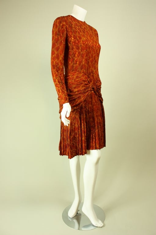 Bill Blass dress dates to the 1980's and is made of burnt orange silk with a leopard print pattern.  Fitted bodice has a round neck and long tapered sleeves.  Pleated skirt has knot detail at center front and center back.  Fully lined.  Center back