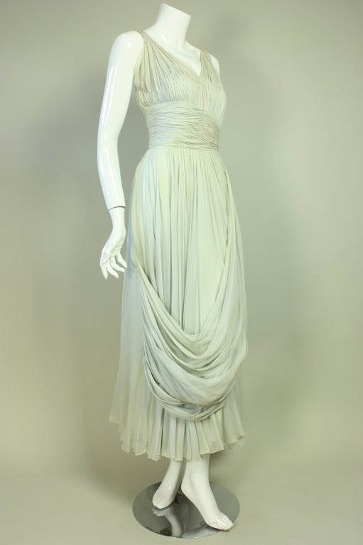 Anonymous 1950's gown retailed at the exclusive Palm Beach boutique Sara Fredericks.  It is made of pale blue silk chiffon that is tightly gathered in the style of Madam Grés.  The dress plays upon the relationship between tight ruching and the