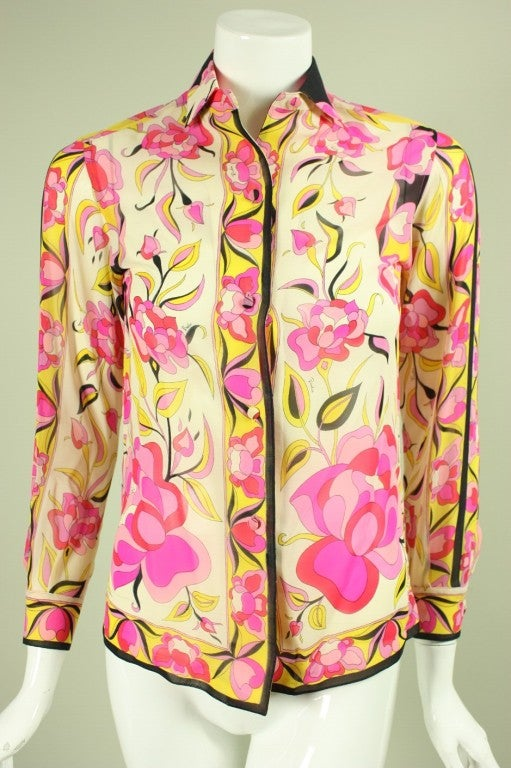 Beautiful blouse from Emilio Pucci dates to the 1960's.  It is made of printed silk chiffon in shades of red, pink, and yellow.  Turn down collar.  Long sleeves with button cuffs.  Button front.  Unlined.