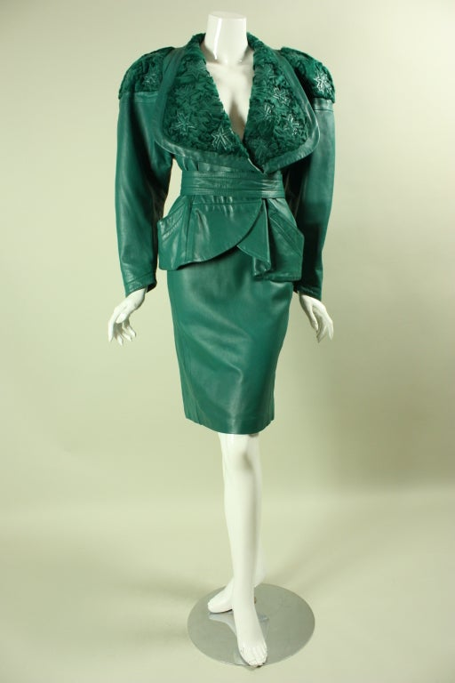 Vintage Jean Claude Jitrois emerald green leather suit dates to the 1980's.  It has an extra wide broadtail collar with abstracted stars appliqued throughout.  Extremely padded shoulders.  Fitted skirt has center back vent and zippered closure.