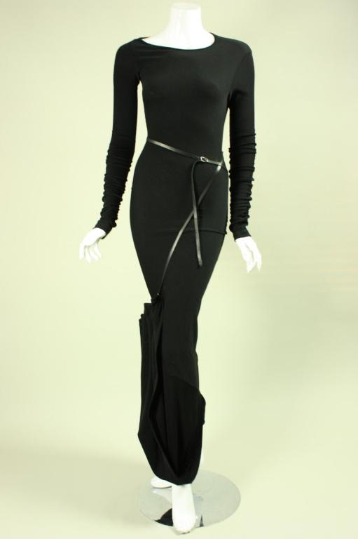 Black bias-cut wool gown from Jean-Paul Gaultier.  Gown has extra-long bunched sleeves and has a train that is gathered to the front and is secured with a belted black leather strap.  No closures.  Unlined.