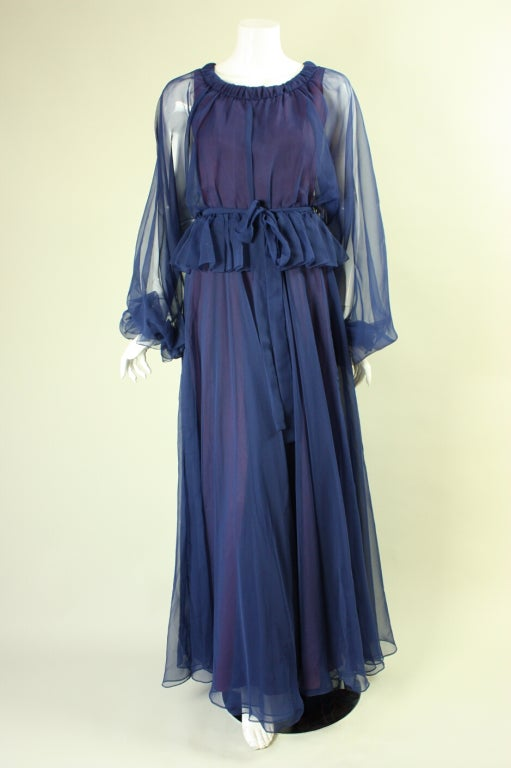 Jean Varon blue gown dates to the 1970's and is made of transparent chiffon that is lined throughout the body.  Round neck.  Overly long sleeves bunch up at the wrists, which have elastic bands.  Peplum detail at hip.  Detached belt can tie at the