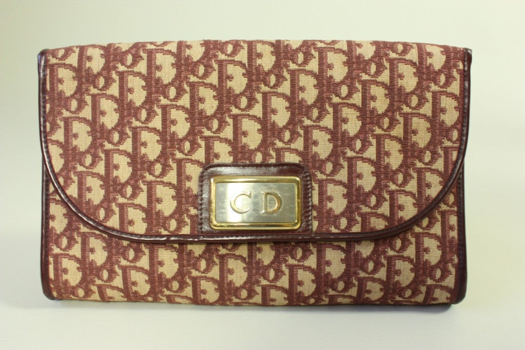 Christian Dior handbag dates to the 1970's and is made of beige canvas with a burgundy monogram print.  It has a fold over snap closure and a gold-toned chain metal double strap.  Leather lined with no interior pockets.  Matching change purse has