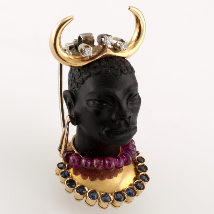 """FANTASTIC RARE HORNED BLACKAMOOR BROOCH IN 18KT GOLD WITH A RUBY BEAD NECKLACE AND A BREAST PLATE COMPLETED BY A COURSE OF BEZEL SET SAPPHIRES. APPX. 1 1/2"""" LONG.  Ca '1950"""