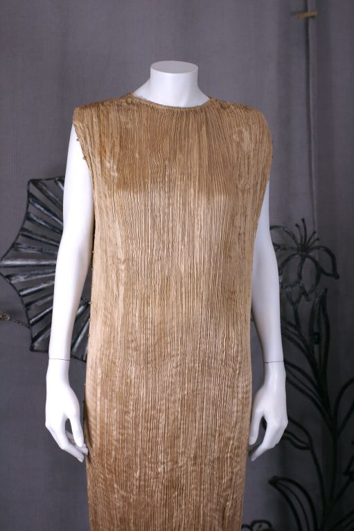 This dress is made of finely pleated cafe au lait colored silk with silk cording along side seams and clear striped glass beads threaded through the cording. <br />