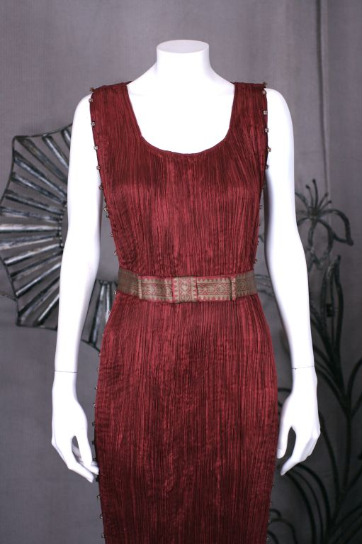 This dress is made of finely pleated claret colored silk with silk cording along side seams, and multicolored glass beads threaded through the cording. The beads are amber glass with white striations. Hand painted label reads