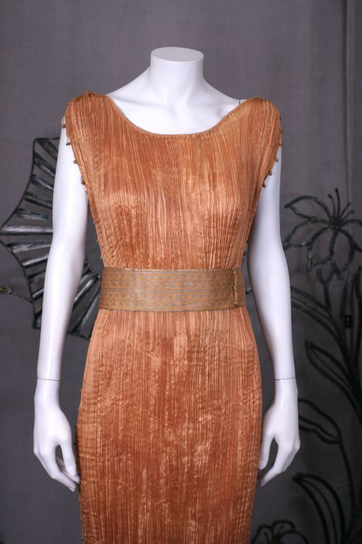 This made This dress of finely pleated apricot colored silk with silk cording along side seams, and multicolored glass beads threaded through the cording. <br />