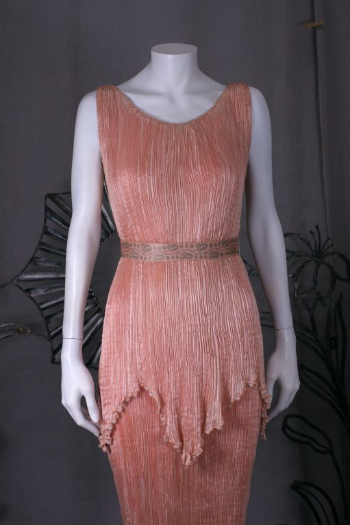 This dress is made of finely pleated  shell pink colored silk with silk cording along side seams ,shoulders , and tunic hem, and  mat frosted colored glass beads threaded through the cording.