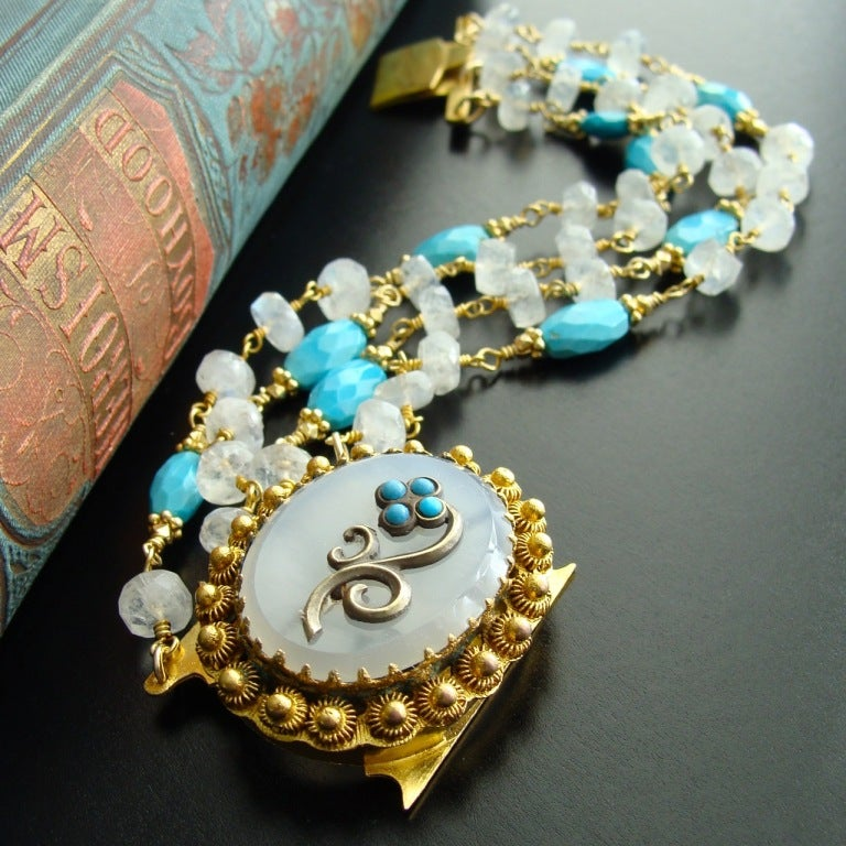 Four strands of hand-linked blue flash moonstone rondelles dotted with  every the popular Sleeping Beauty turquoise faceted oval nuggets are the perfect compliment for this antique Georgian Pinchbeck clasp.  The agate clasp features a lovely little
