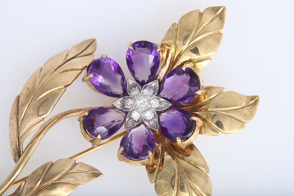 a fancy retro diamond and amethyst brooch featuring a stylized floral inspired design centrally set with 7 round brilliant cut diamonds weighing approx. .25cts total framed with 6 pear shaped amethyst weighing approx. 10cts total in a hand made 14k