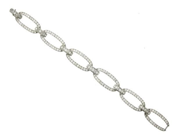 Diamond bracelet by Georges Fouquet, French, circa 1920.  A platinum bracelet composed of six oval links joined by six curved bar shaped links including an integrated clasp, set with one hundred seventy four round old cut diamonds in millegrain bead