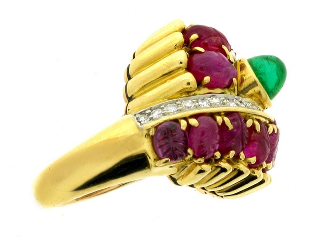 Marchak cabochon emerald, carved ruby and diamond ring. Set centrally with a round cabochon natural emerald with no colour enhancement in an open back rubover setting with an approximate weight of 1.00 carats, bordered by two rows of fourteen oval