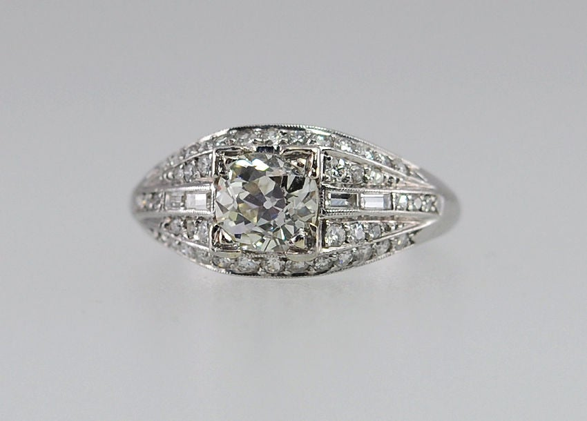 Platinum ring with all the great Deco elements. A stunning mix of full cuts and baguette cut diamonds, surrounding a center 1.05ct old european cut diamond. The color is K, the clarity VS1. This is a real beauty!
