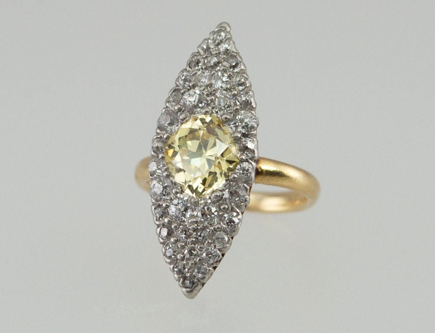 According to the Tiffany appraisal,  this ring is Tiffany circa 1905 It is a navette shape, with a 1.30 ct Old European cut Fancy Yellow center diamond. The rest of the mounting is filled with numerous old European cut diamonds, all set in platinum,