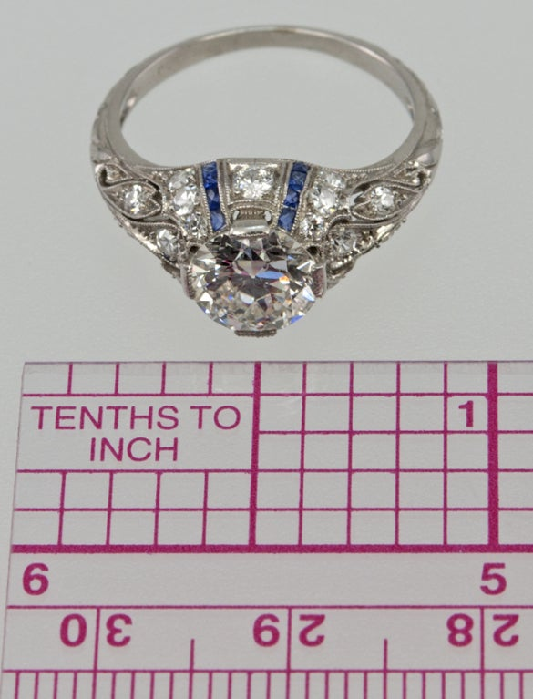 Beautiful, elegant ring!  This ring has very decorative filagree cut out work, that is diamond encrusted with full and single cut diamonds.  The center old european cut diamond is 1.24 carats G-Vs2 with an EGL certificate. There are four channels of