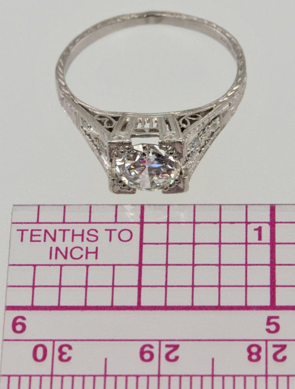 Platinum ring with amazing engraved detail literally on every surface! This ring is SO Deco! There is an old european cut diamond in the center, G-VS1 with an EGL certificate.  On each side is a single cut diamond and a crazy great gallery!.  Great