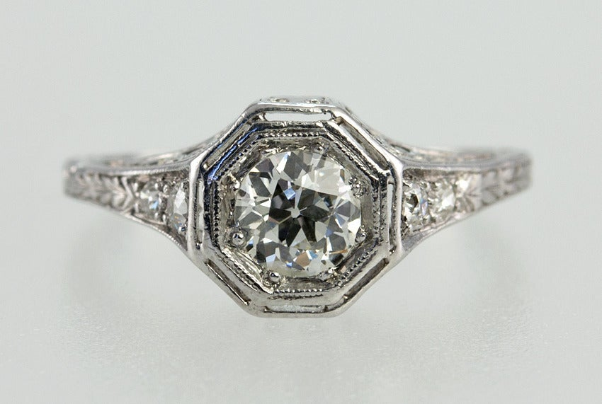 Platinum engraved ring with .75 carat center old european cut diamond set into an octagonal bezel.  The color is approximately H-I and the clarity is SI2. There is a full cut and single cut diamond on each side.  This is a lovely period engagement