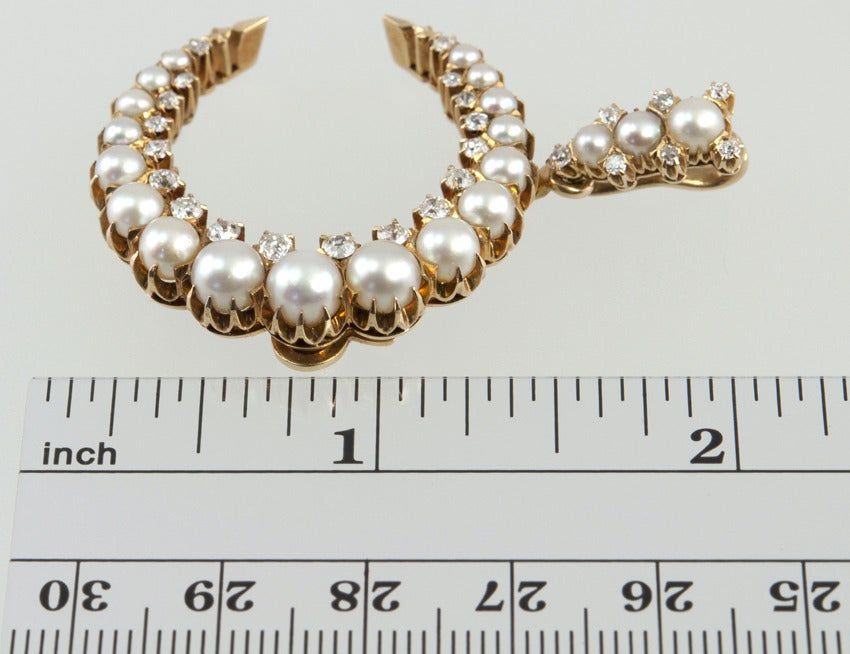 Antique Victorian crescent brooch and pendant in 14 karat yellow gold. This amazing piece can be worn as both a brooch and pendant.  The piece is comprised of 20 pearls and 25 Old European Cut diamonds, approximately 1 carat in total diamond weight.