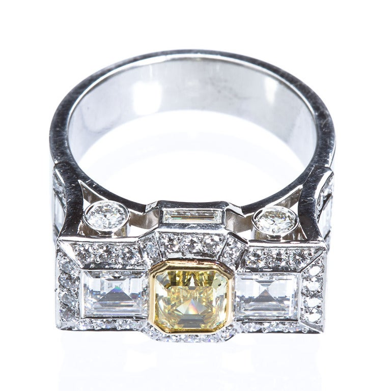 One of a kind handmade platinum and 18k gold flush head three-stone diamond ring contains a 0.87ct fancy intense yellow VS1 clarity emerald cut diamond set between two ~0.80 ctw step cut colorless diamonds of high clarity. The rim of the head is