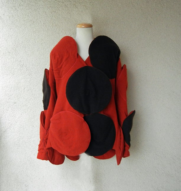 Description: Circa early 90's Issey Miyake unique jacket adorned with strategically placed black and red beret hats. Fashioned of wool with geometric motif placement of hats. Hip pockets hidden by the berets.  A longer version (seen in gray) is part
