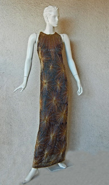 """Documented gold beaded """"fireworks"""" gown from Halston's Fall 1980 collection. Entire outfit seen on page 197 of the book entitled """"Halston An American Original"""".    Unworn 2 piece fully beaded silk beaded gown in a starburst pattern with matching"""