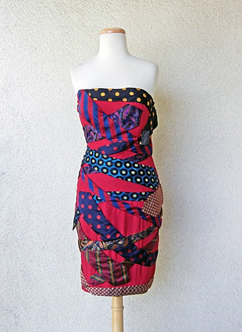 The is a Moschino Couture made in Milano circa 80's tie dress by Franco Moschino. Fashioned in all silk on a base of deep red silk and overlaid in vintage ties from the 60's and 70's placed diagonally and asymmetrically throughout the dress.  A