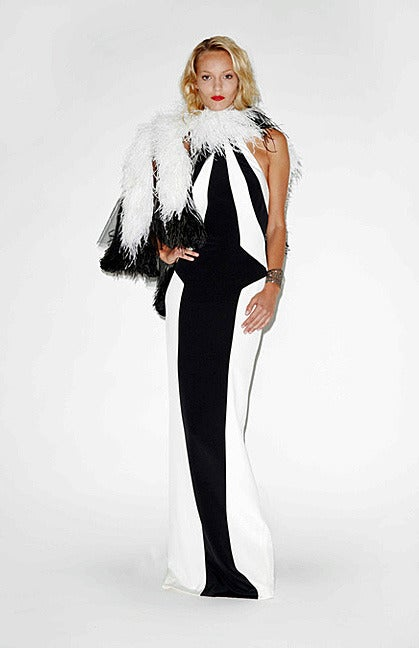 A bold entrance making creation by fashion designer L'Wren Scott (1967-2014). Known for her impeccable taste and style she was known for long slenderizing silhouettes, femininity and impeccable elegance.  A halter style black and white stretch silk