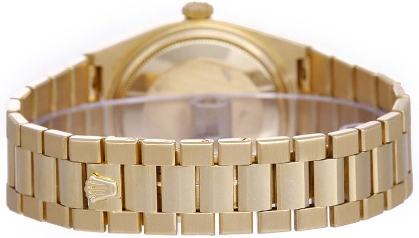 18k yellow gold case with fluted bezel. White dial with raised gold stick markers. 18k yellow gold hidden-clasp bracelet. Quartz movement; quick-set; sapphire crystal. Pre-owned with box and books.