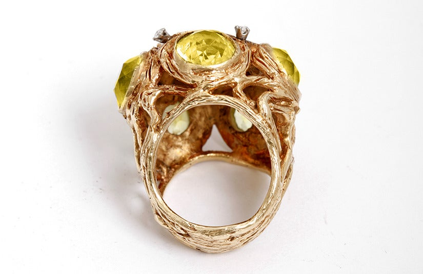 Make a statement wearing this dramatic 14k yellow gold ring featuring 6 peridot stones and 5 diamonds. The ring is apx. 1 inch in diameter.  The ring is a size 6  with a total weight of 31.8 grams.