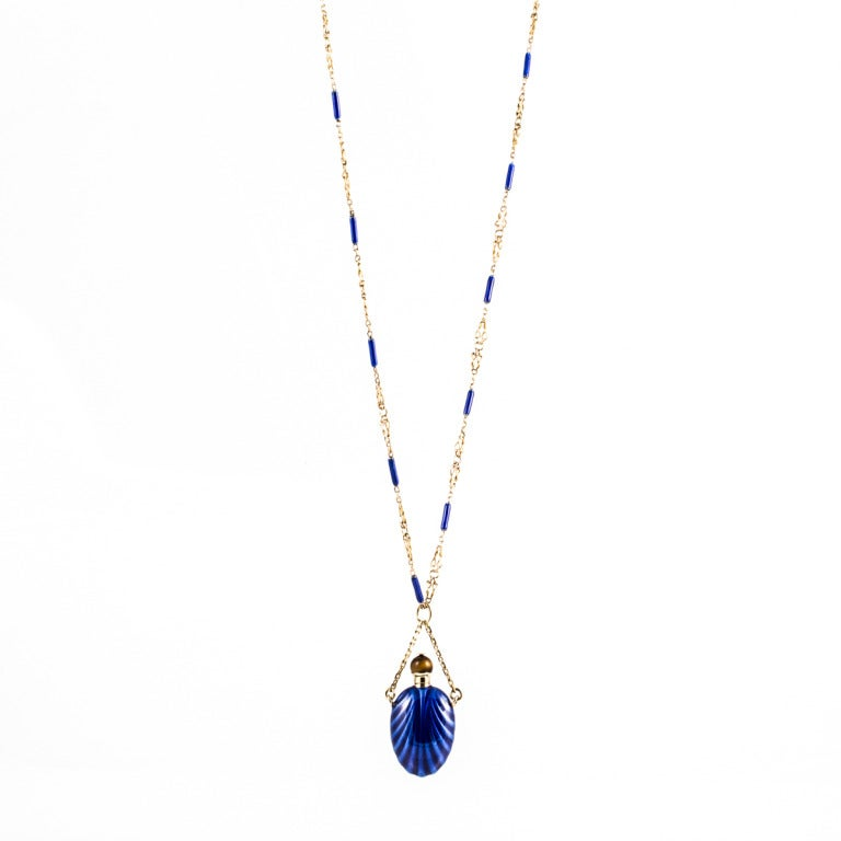 This necklace from the 1960s features an 18k yellow gold and blue enamel perfume bottle pendant with a top that screws on and off for your favorite scent. The matching chain has sections of 18k yellow gold and blue enamel. The top of the bottle is