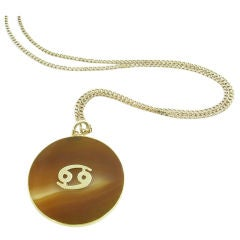 """CARTIER banded agate and gold """"Cancer"""" pendant on a chain."""