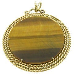A  yellow gold and tiger's eye disc pendant set in twisted gold