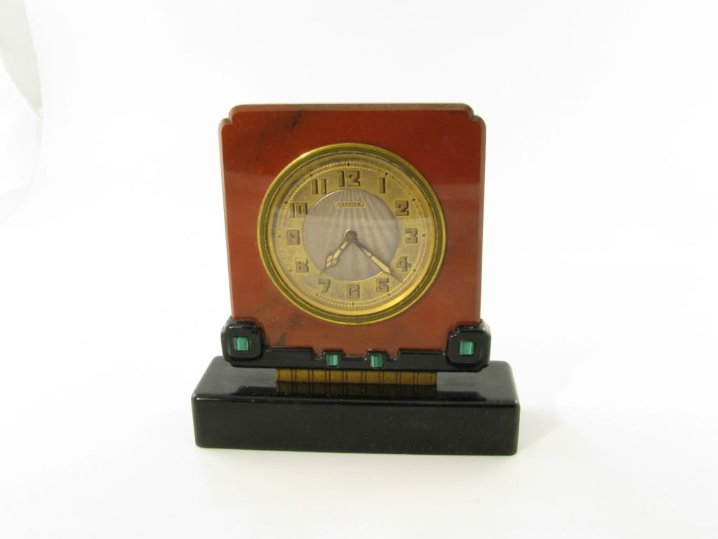 A Cartier clock made from jasper with a black onyx base embellished with malachite.  Circa 1920's, with the original Cartier fitted box.