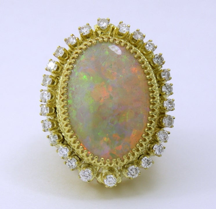 One ladies 18K yellow gold ring set with one amazing oval shaped contraluz opal measuring 30mm X 20mm. With beautiful play of color, the opal is then surrounded by 26 round brilliant cut diamonds weighing 2.75ct total approximate weight, of overall