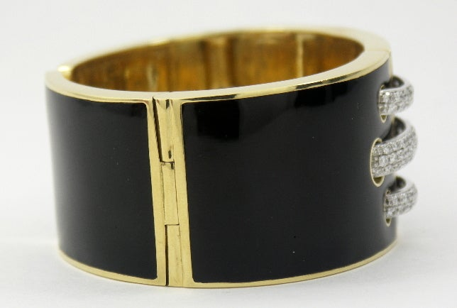 An exquisite bracelet by David Webb in 18K yellow gold. Measuring 1 1/4 inches wide, it is beautifully enameled in black with a high gloss. Running through the middle of this amazing piece are three platinum sections, that appear to be threaded