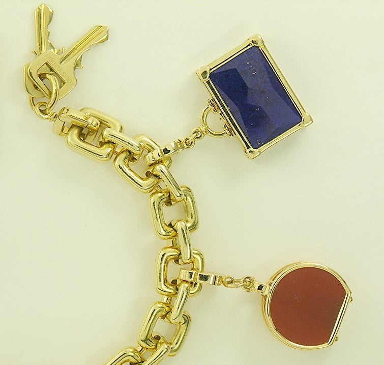 """Original 18K Gold Louis Vuitton charm  bracelet with lock and key, and with seven original Louis Vuitton 18K Gold charms.  The bracelet measures 7 5/8"""" long. The Eiffel Tower charm in the center is set with 16 diamonds and measures 1 3/8 inches"""