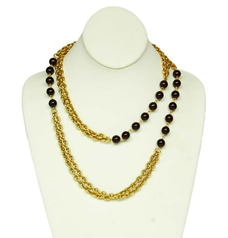 CHANEL Gold Chain Link Necklace W. Red Gripoix Beads c. 1970s/80s Age: 1970s/80s Made in France Materials: goldtone chain, red poured glass (gripoix) beads. Features attached double strand gold chainlink necklace with sections of red beads.