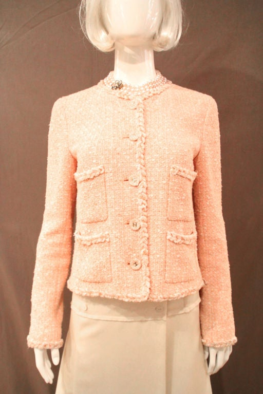 This CHANEL 07P Peach Tweed Boucle Jacket evokes the timeless and classic design of Chanel. As part of the 2007 Chanel Fall/Winter Collection, this item is a must-have.<br />