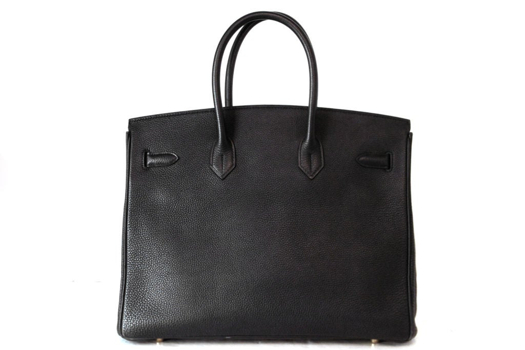 This HERMES Black leather 35 cm Birkin Bag is the epitome of style and sophistication.  The most coveted handbag in the world.  Features black textured leather, which we believe it to be togo leather. Golden hardware.  Hardware on the strap engraved