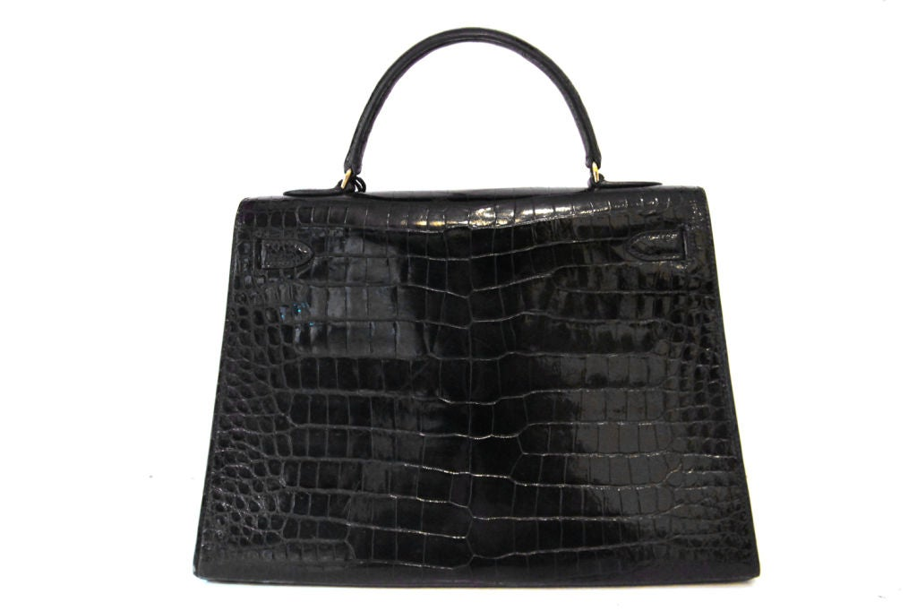 A timeless classic, this Vintage Hermes Kelly 32 cm Bag is a must-have addition to any Hermes lover's collection  Made in the most luxurious, black exotic crocodile with golden hardware. Top handle with front flap and twist lock closure.  Hardware